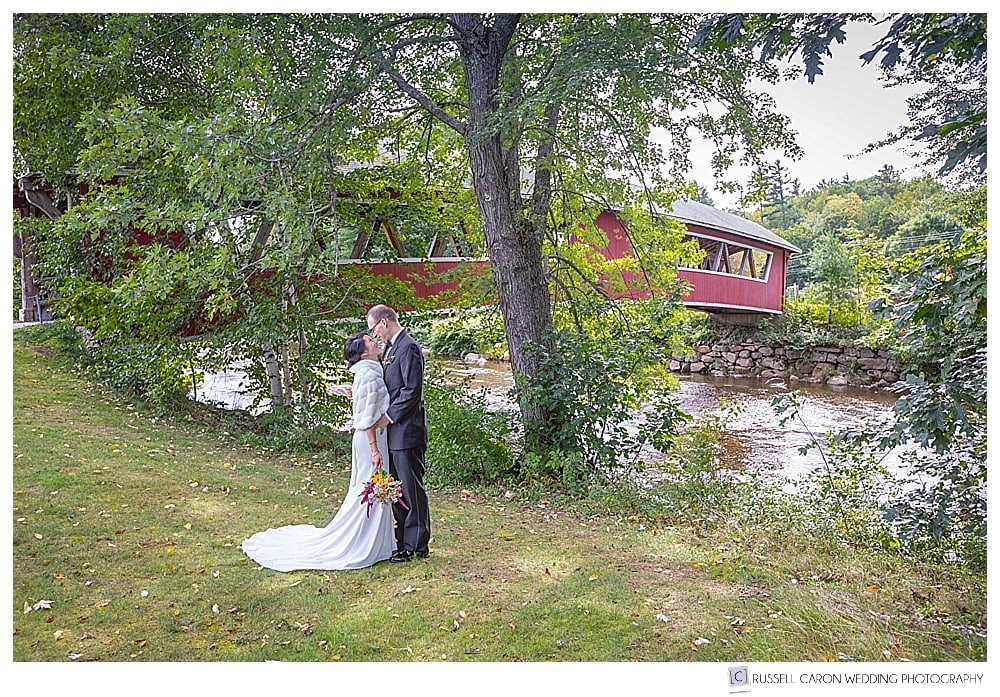 bride and groom kissing on the bank of the Saco River in Jackson New Hampshire
