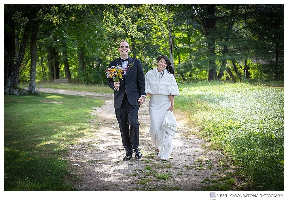 bride and groom walking together, while groom holds bridal bouquet