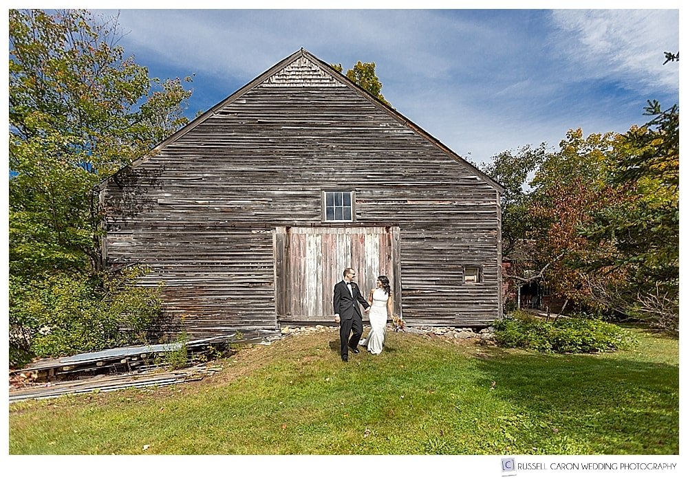 Bride and groom in front of weathered barn at Thompson House Eatery, Jackson, NH
