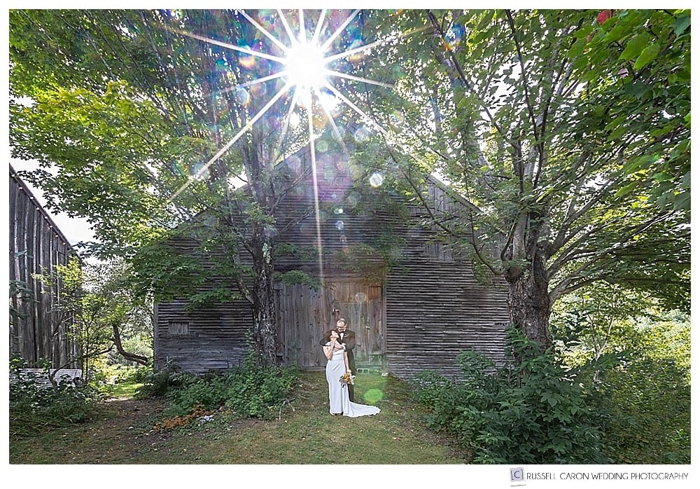 Bride and groom standing in front of weathered barn with sun flare, at Thompson House Eatery, Jackson, NH,