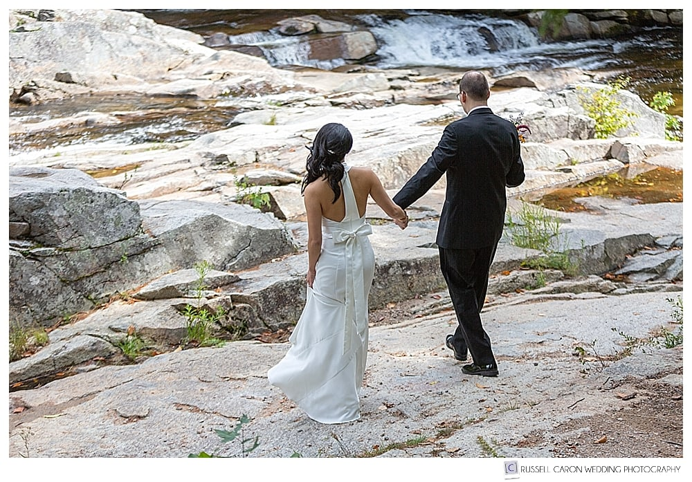 Bride and groom walking on the rocks at Jackson Falls, Jackson, NH