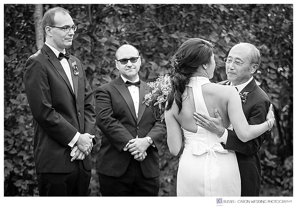 bride and her father looking at each other, groom and best man look on
