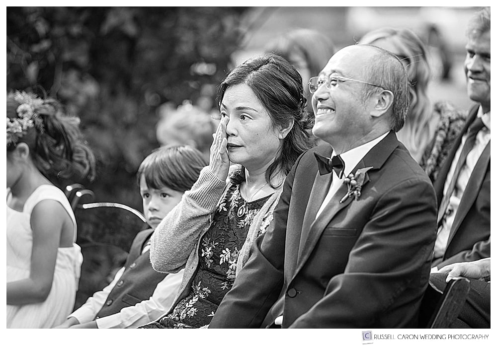 black and white photo father of the bride smiles during wedding ceremony