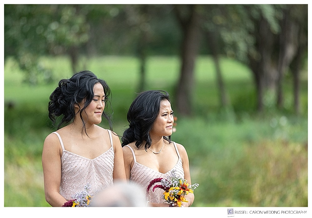photo of two bridesmaids at outdoor wedding ceremony
