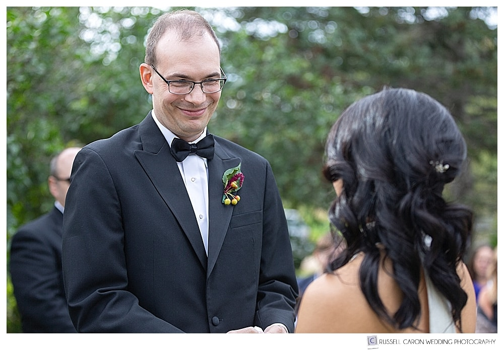 Photo of a groom looking at his bride