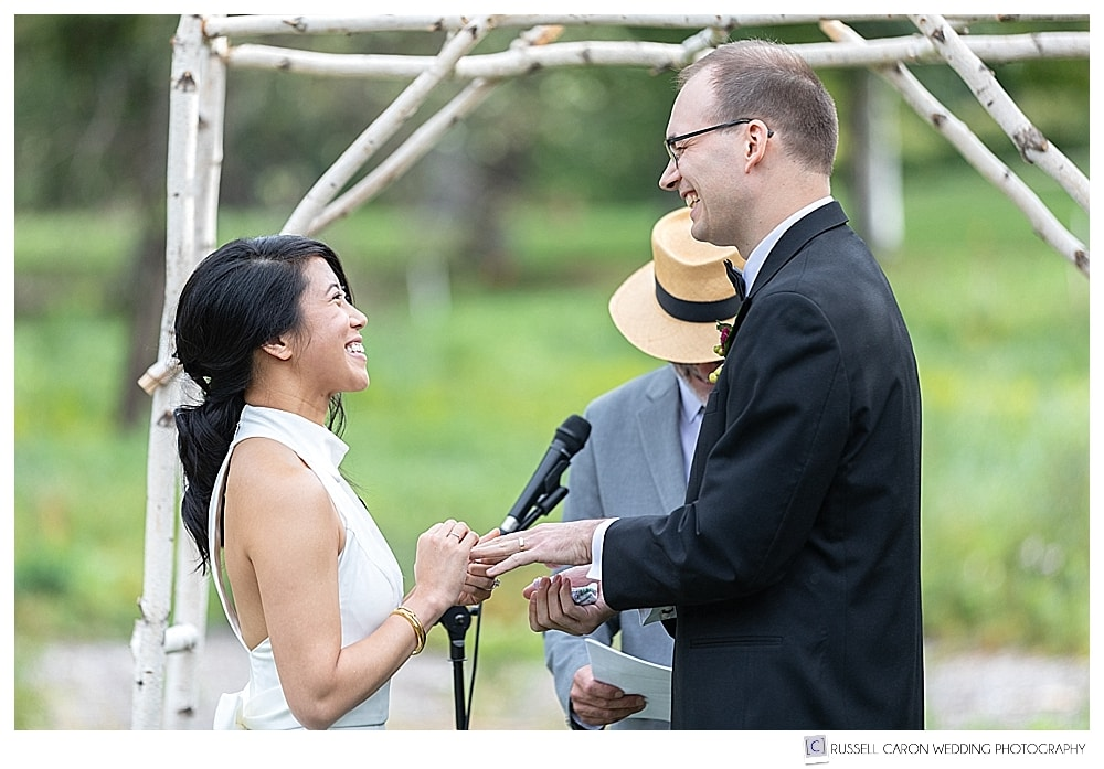 bride and groom smiling at each other as bride puts ring on groom's finger