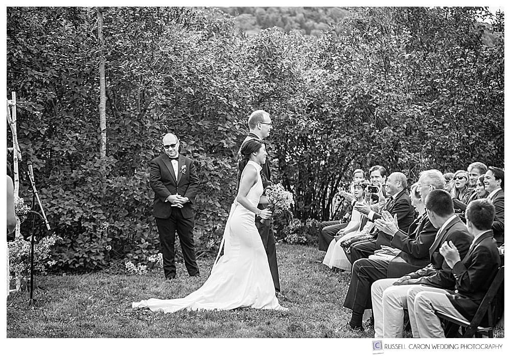 black and white photo of bride and groom starting their recessional