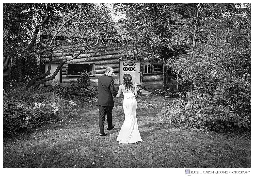 black and white photo of bride and groom as they walk towards the Thompson House Eatery in Jackson, NH