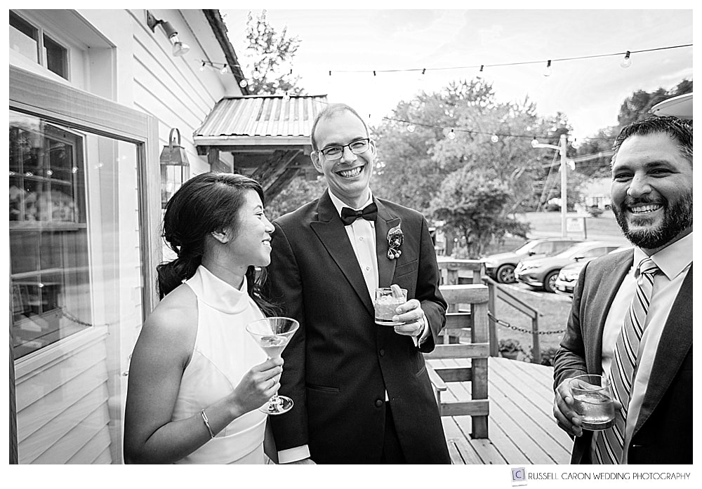 black and white photo of bride and groom holding drinks