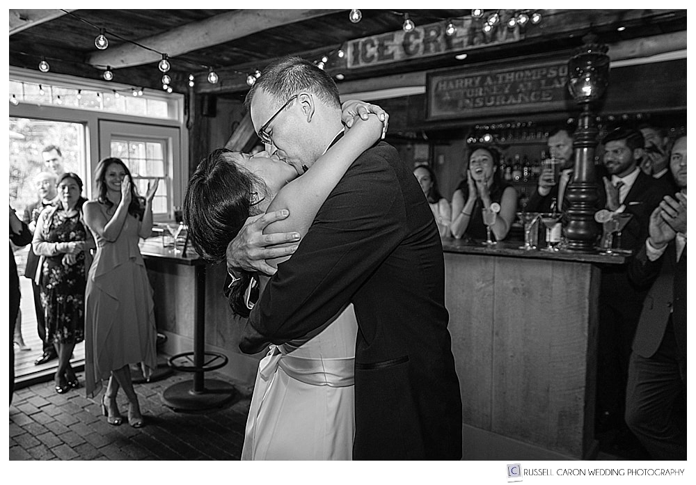 black and white photo of bride and groom kissing after their first dance
