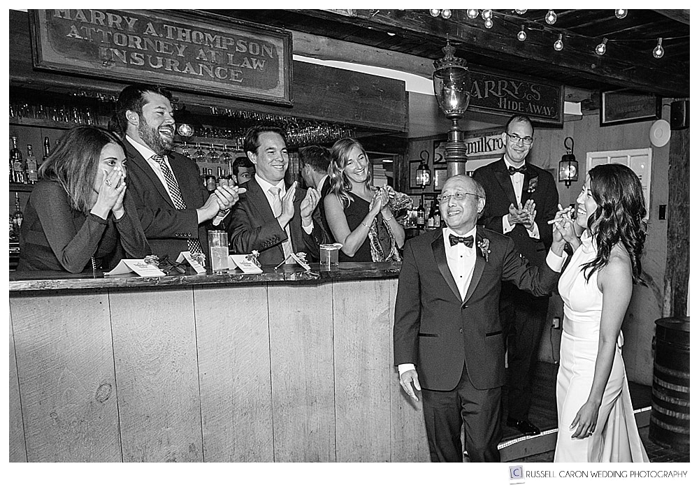 black and white photo of bride with her father while guests clap