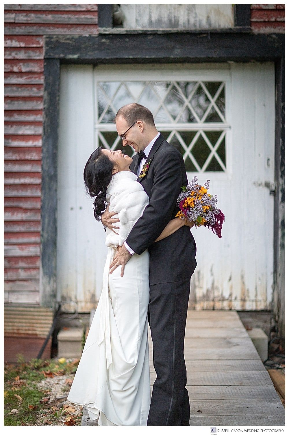bride and groom kissing in front of a white door