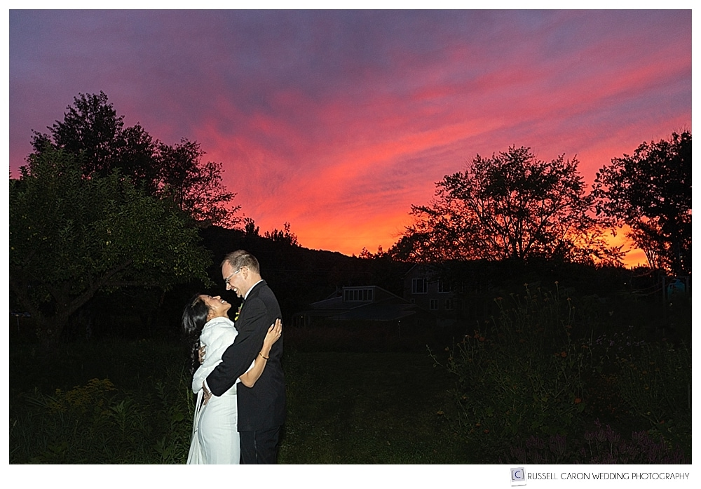 bride and groom photographed in bright pink sunset