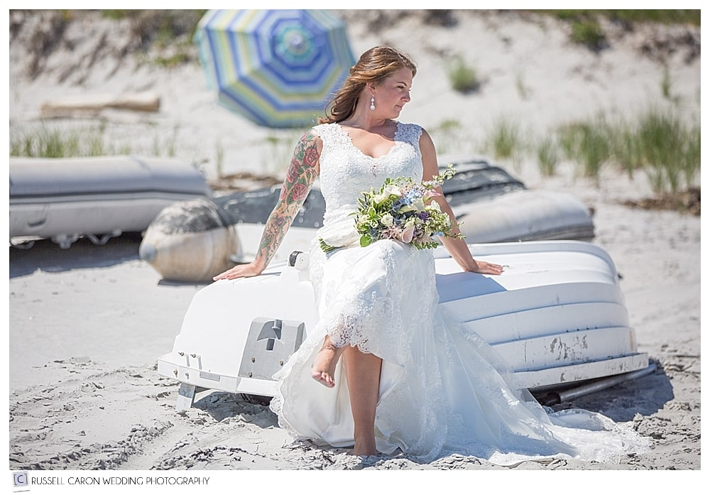 bride-sitting-on-a-dinghy-on-the-beach