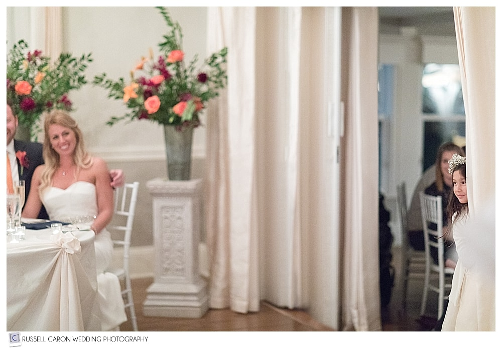 flower girl peeking in at bride and groom during wedding reception