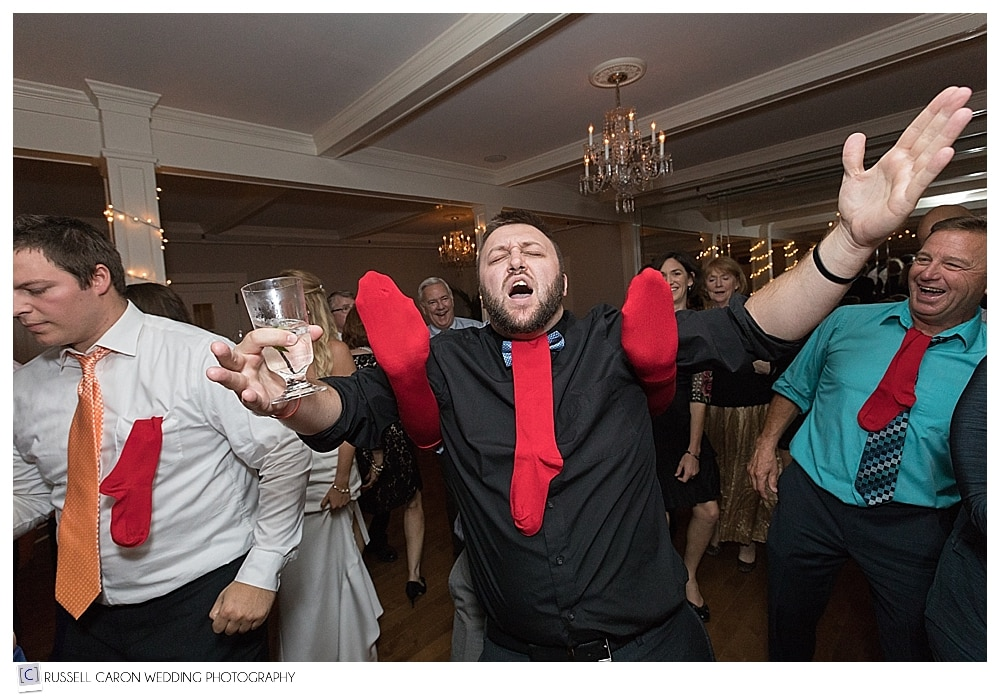 wedding guest dancing with red socks on hands