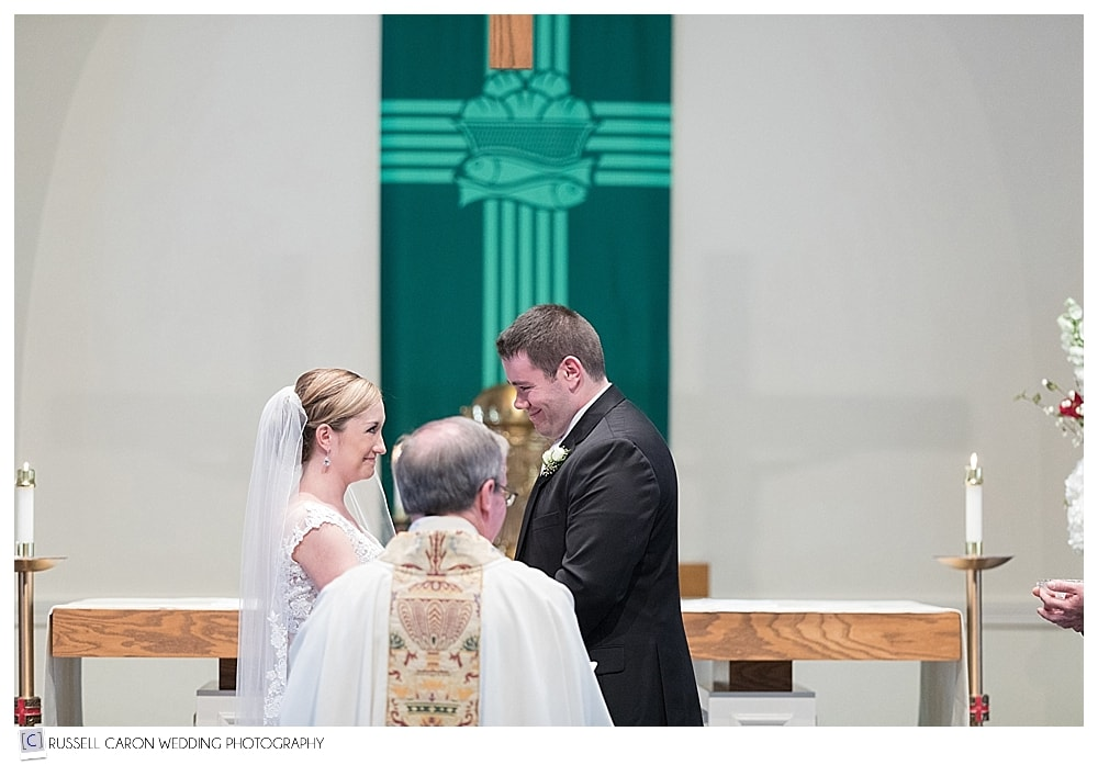 bride and groom before priest during wedding ceremony