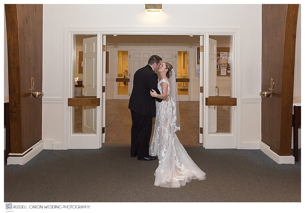 bride and groom kissing at the door of the church