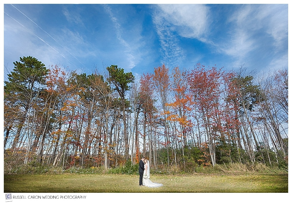 bride and groom in front of trees of fall foliage