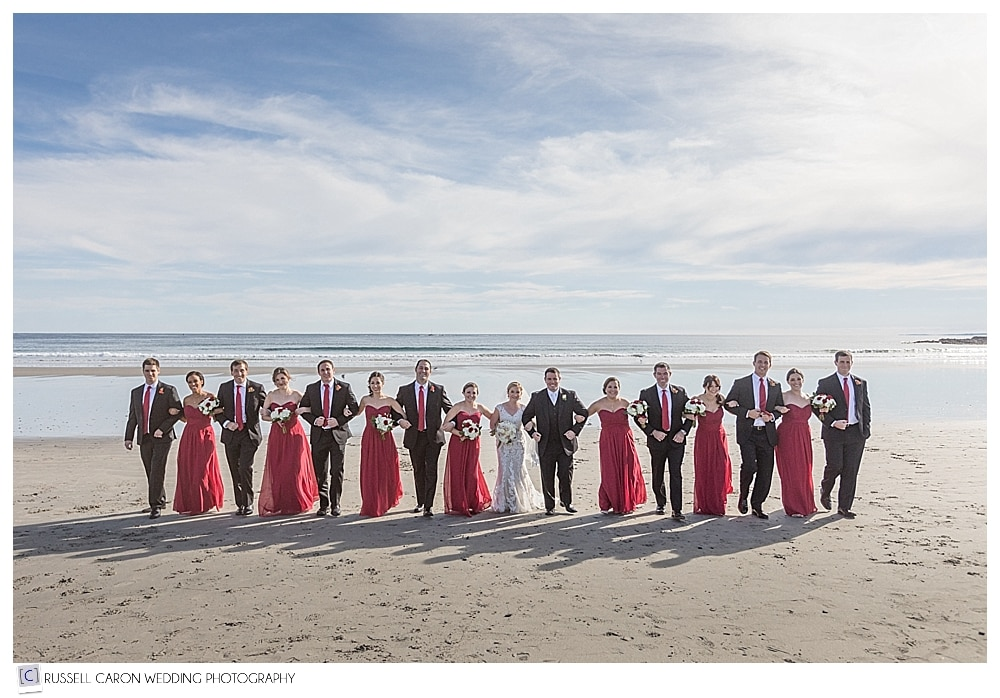 bridal party walking arm in arm on the beach
