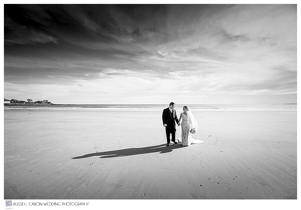 bride and groom walking hand in hand on the beach