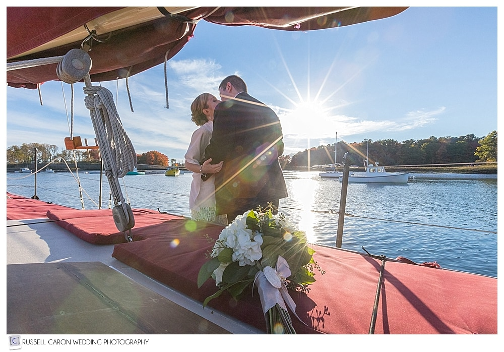 bride and groom kissing on sailboat