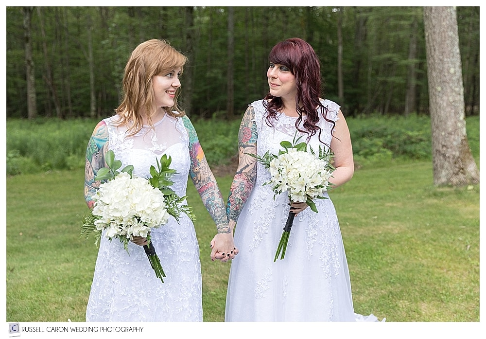 two brides standing and looking at each other