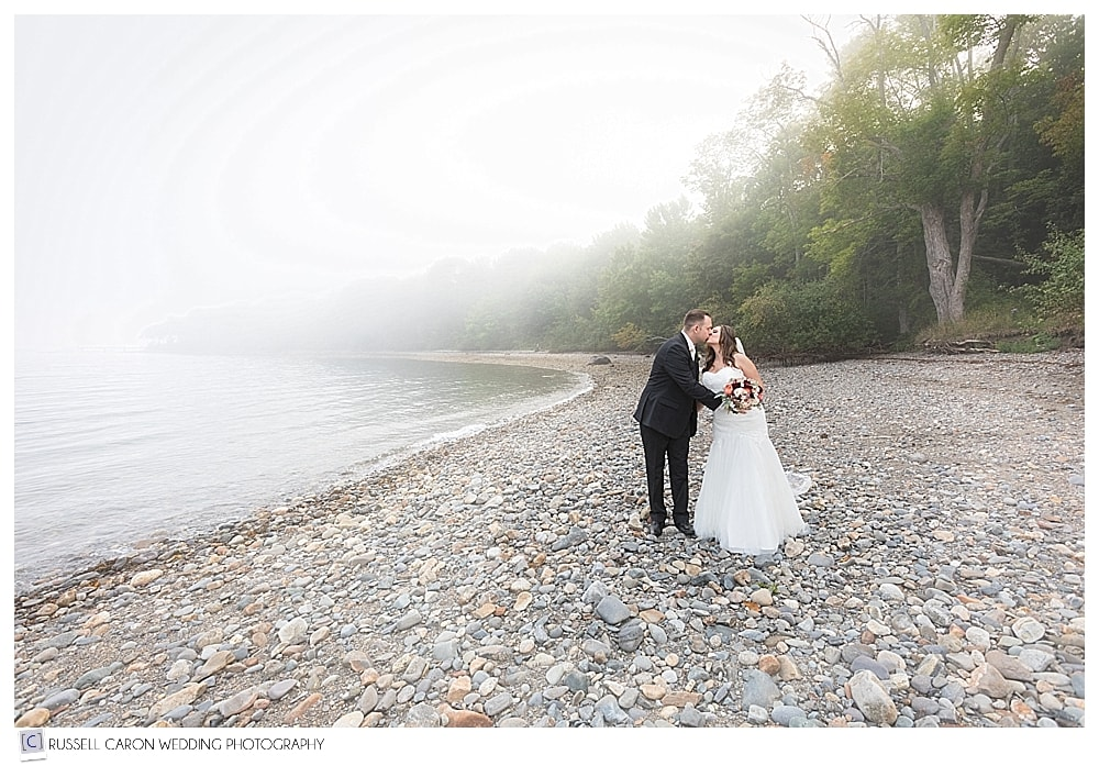 bride and groom kissing on a foggy Maine beach
