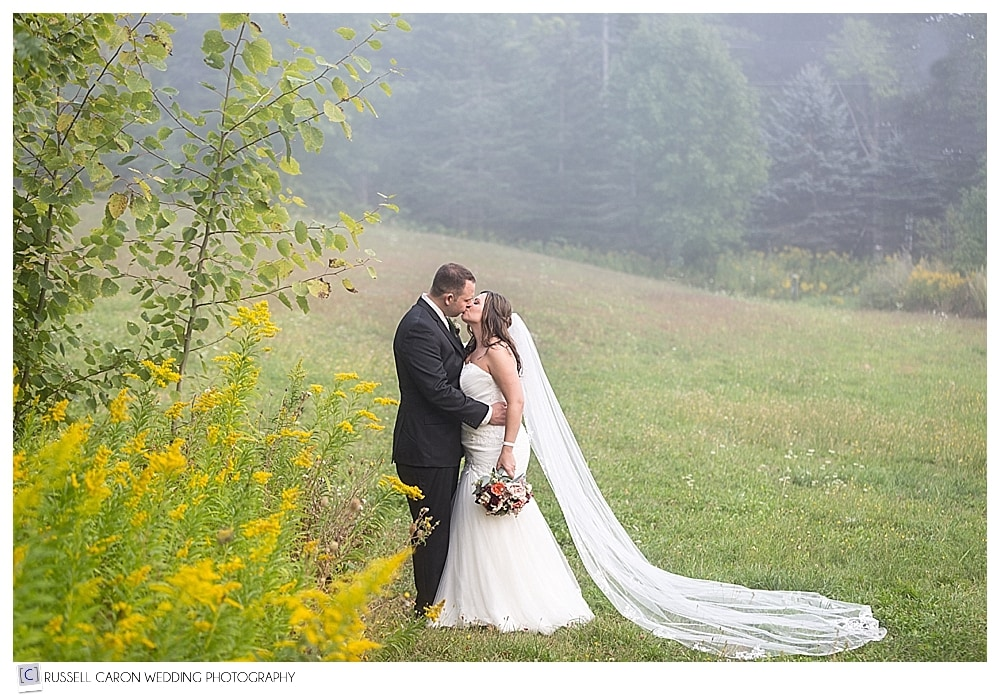 bride and groom kissing in a foggy field