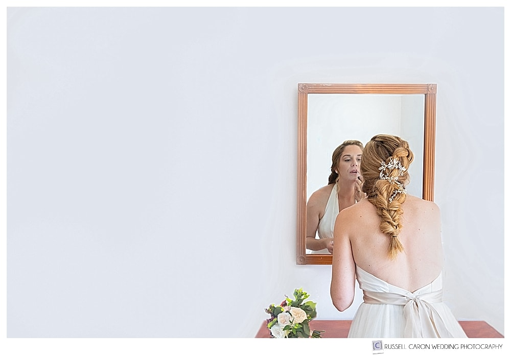 bride putting on lipstick, reflected in mirror