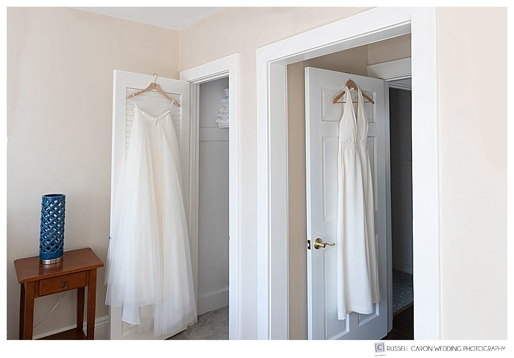 wedding jumpsuit and tulle skirt hanging on doorways