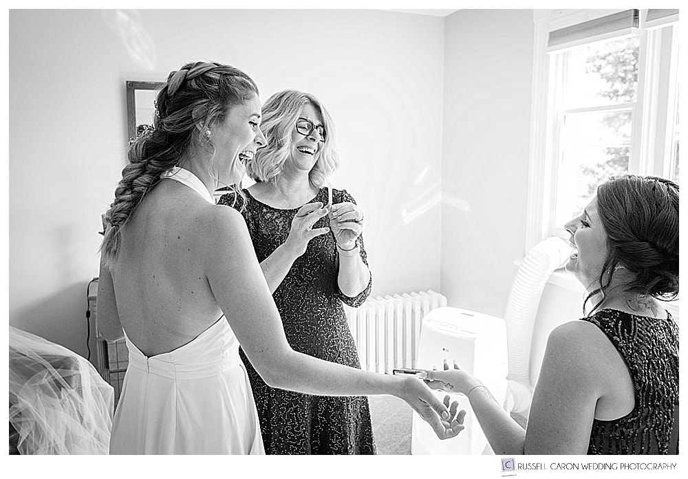 black and white photo of bride prepping with her mother and sister
