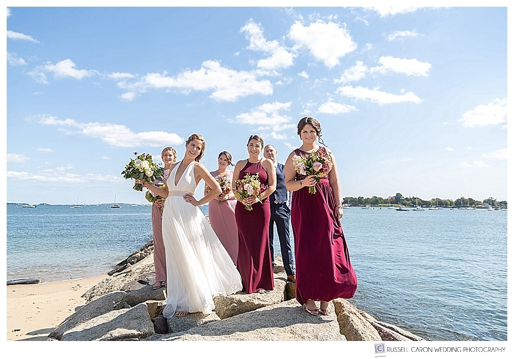 Bride, bridesmaids, and bridesman standing together on a jetty in Beverly, MA