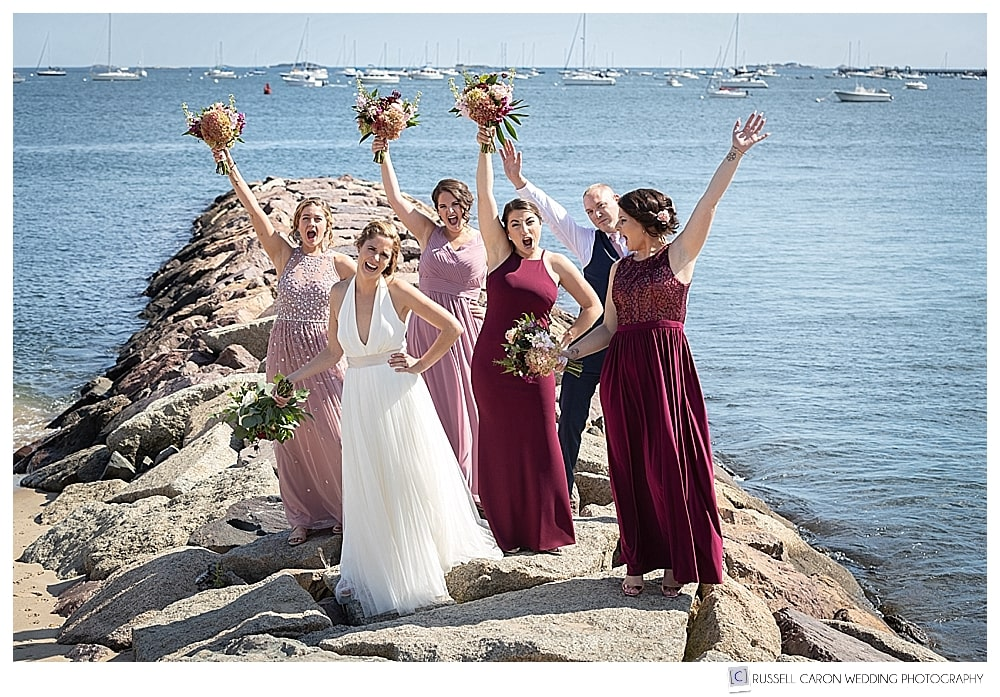 Bride with bridesmaids and bridesman cheering her on a jetty