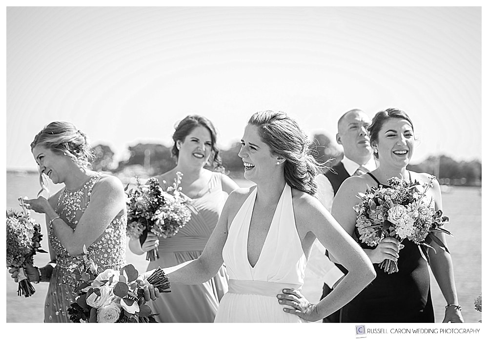 black and white photo of bride laughing with her bridesmaids and bridesman