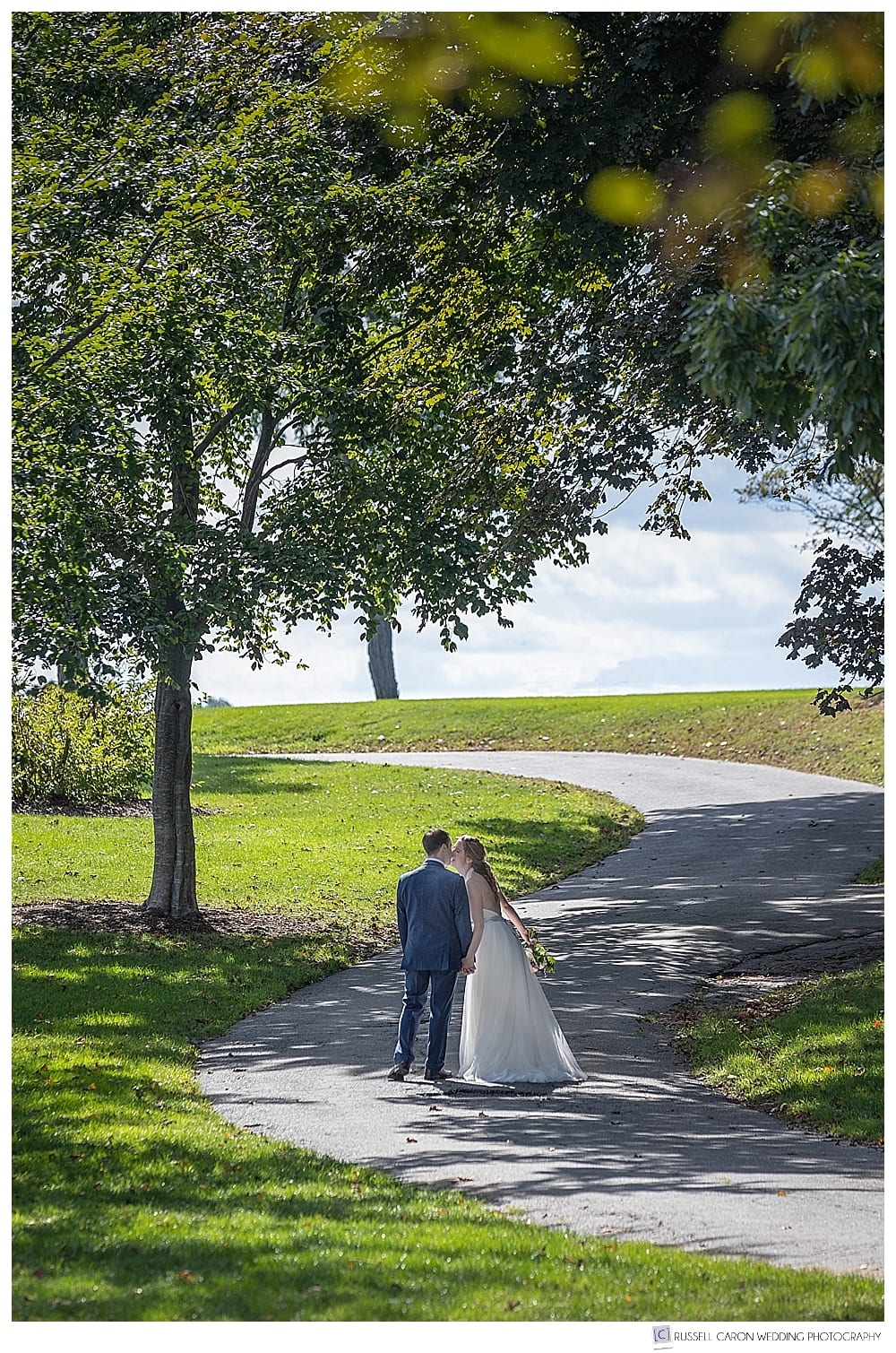 bride and groom walking up curved path, kissing
