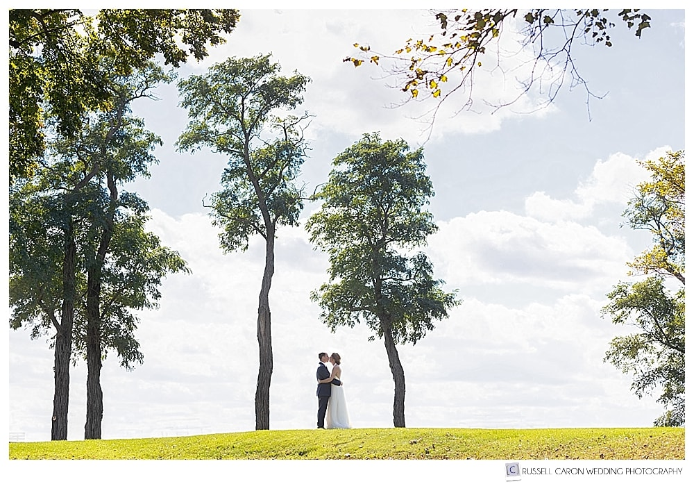 bride and groom kissing between two trees