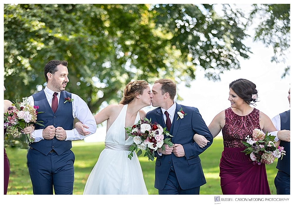 bride and groom kissing, while bridesmaid and groomsman look on
