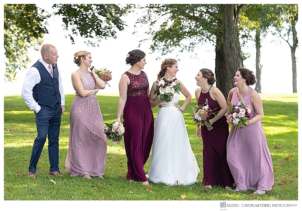 bride and bridesmaids and bridesman laughing