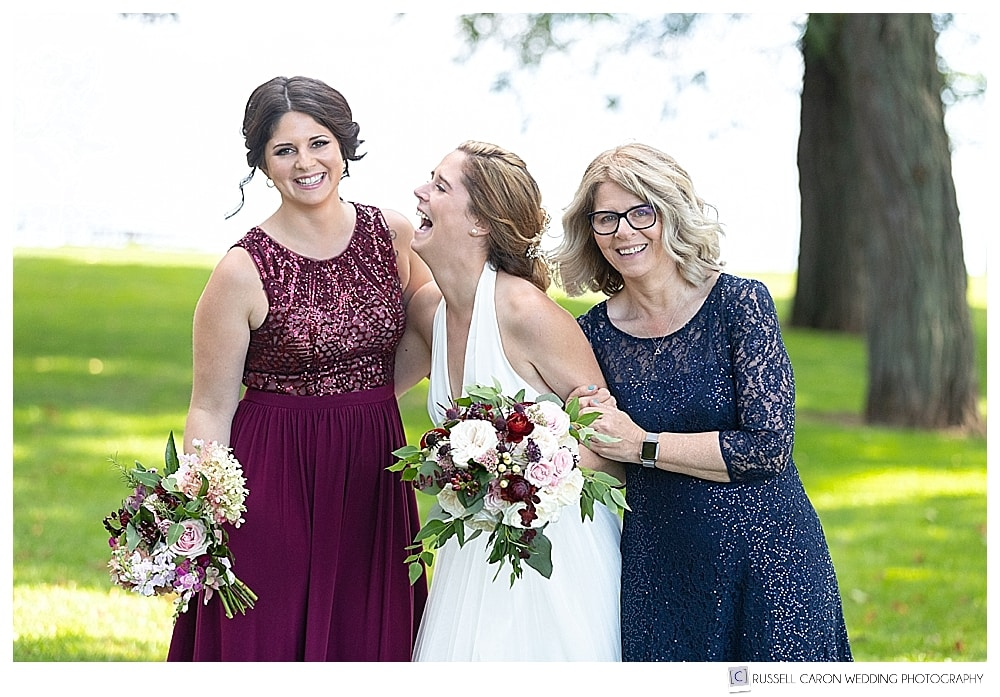 bride laughing with sister and mother