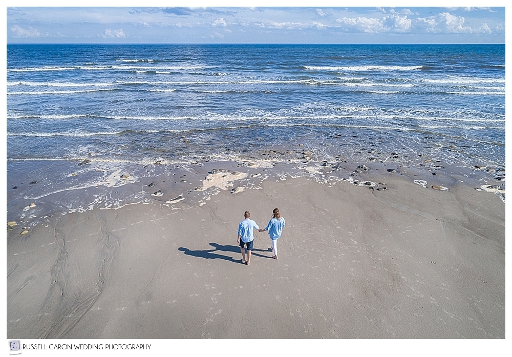 couple walking hand-in-hand toward the ocean, maine drone engagement photography