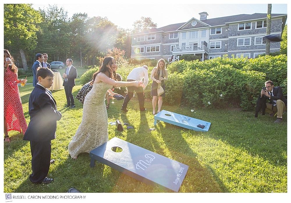 bride-playing-corn-hole-during-wedding-reception