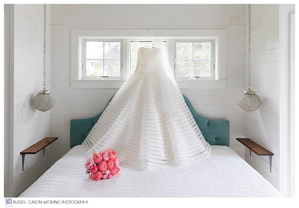 wedding dress hanging over bed