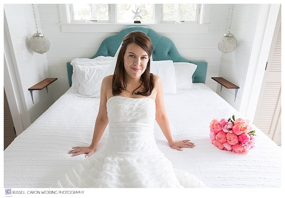 photo of bride sitting on a bed