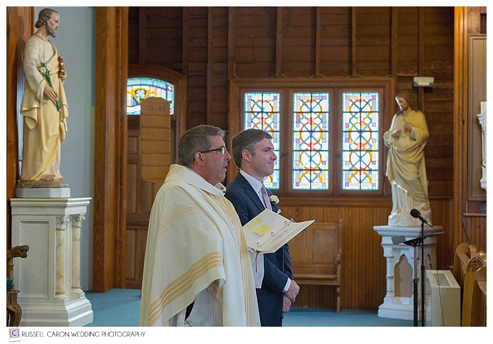 Priest and Groom waiting for bride at the altar of Our Lady Queen of Peace Church