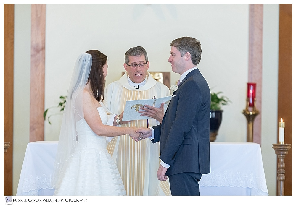 Bride, groom, and priest during wedding ceremony