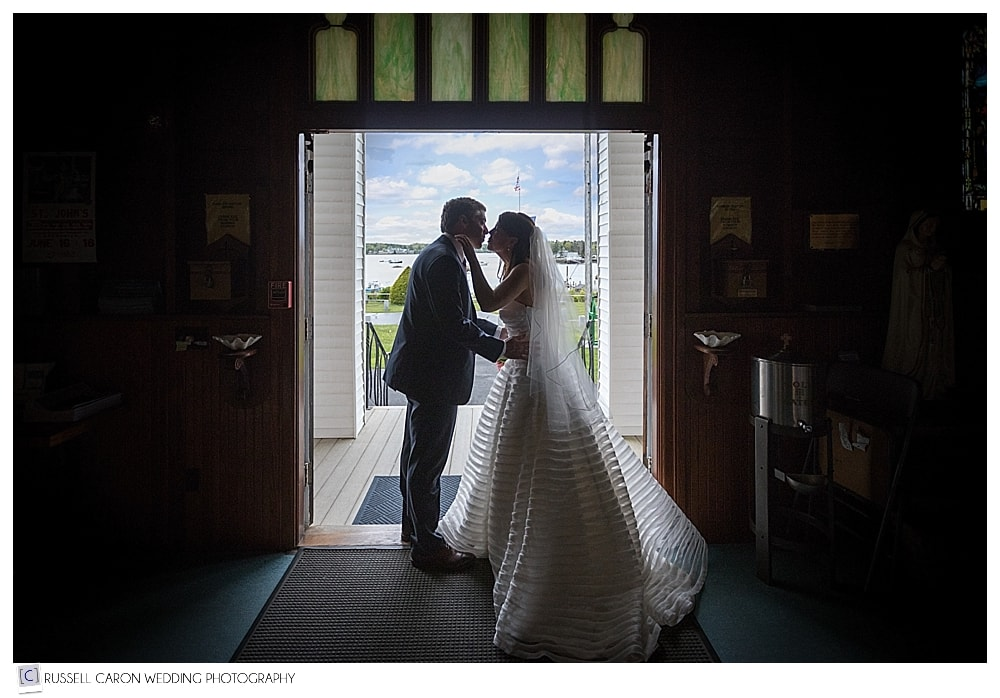 bride and groom kissing in the doorway of Our Lady Queen of Peace Church