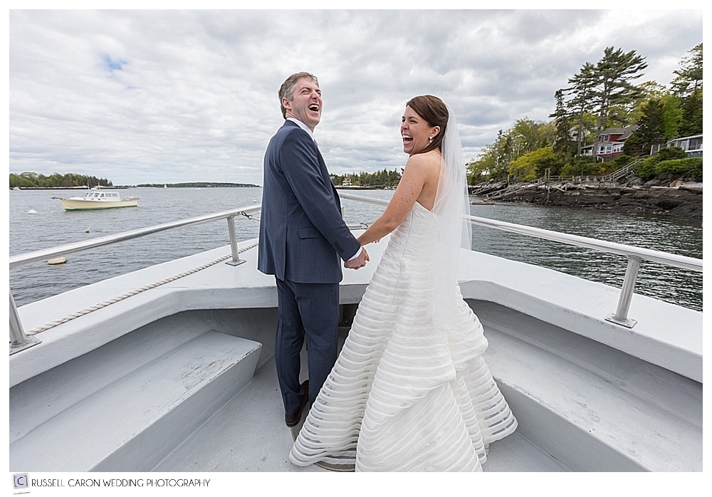 bride and groom at the bow of the boat