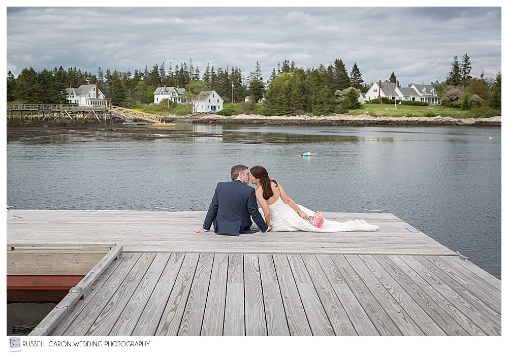 bride and groom sitting on a dock in Southport, Maine