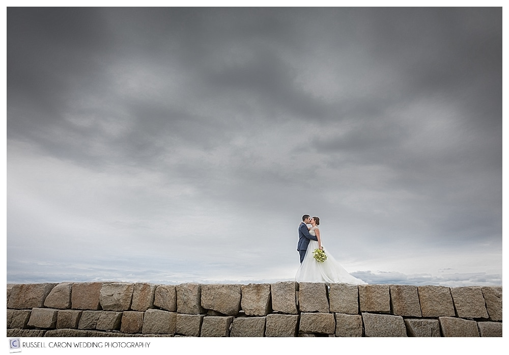 bride and groom on the Kennebunkport Maine breakwater, with dramatic skies